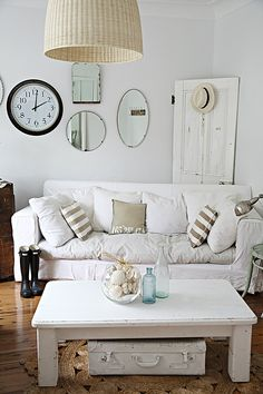 White rustic living room with salvaged wood door, vintage mirrors, white painted suitcase and striped pillows