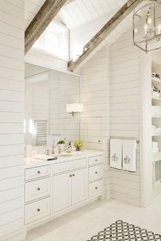 White master bathroom features a shiplap vaulted ceiling dotted with rustic wood beams accented ...