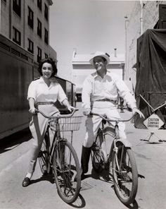 """Elizabeth Taylor and Dana Andrews ride bikes.Dana Andrews and Elizabeth Taylor ride bikes in Sri Lanka - or more precisely the Paramount backlot - between scenes for 1954's """"Elephant Walk."""" On"""