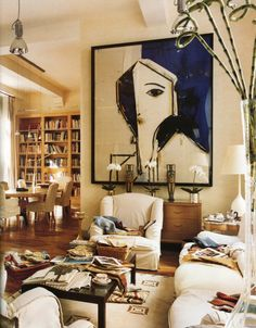 Gorgeous lounge dining room love massive artwork in blue and white over console table and oval dining table against library bookshelves