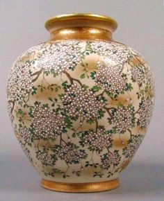 A museum quality Japanese satsuma vase with raised floral enamel decoration and brocade design neck and base, from the Meiji Period. Signed. 6.25 inches high x 5.25 inches deep.