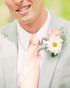 A boutonniere with a rose, a daisy, and two sprigs of fresh lavender