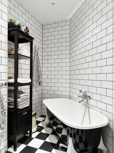 Czarna wanna w biało - czarnej łazience.   Black bathtub in black and white bathroom