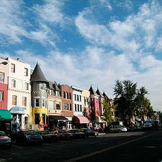 A dozen three to four story townhouses painted bright colors line a street