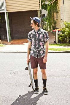 Everything that's trendy in young men's fashion: Floral button-down, five-panel hat, long socks and sneakers, aviators and skateboards.