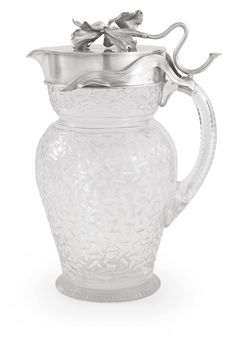 A Fabergé Russian Silver-Mounted Cut Glass Carafe, Moscow, circa 1900, of baluster form, the silver hinged lid topped with chased lily, the flower stem extending to form thumbpiece, the glass body with geometric design of cut trapezoid shapes, the handle with conforming decoration, the interior gilded.