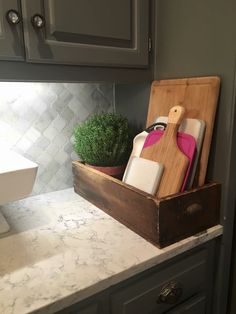 Cute cutting board storage. Use an old wooden crate with some greenery in the back.