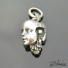 Unique silver pendant - handmade piece. Gouging and details in the form of mechanisms and screws on an android head created with use of a magnifying glass.Length: 28 mmWidth: 12 mmDepth: 18 mmDiameter: 10 mmWeight: 32gJewelry signed with ZAHARIO l...