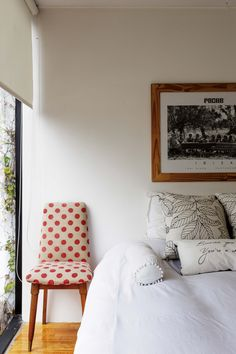Dormitorio principal de un departamento con cama de dos plazas, acolchado blanco, silla vintage (Mercado de Pulgas de Dorrego) y una foto enmarcada de Pacha Ibiza, tomada por el lente de Toni Riera.