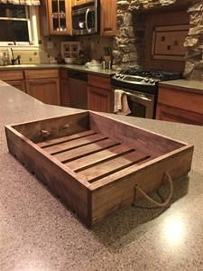 """Antique style wooden serving tray with rope handles. These trays are hand made and hand finished with a medium brown stained finish. The outside dimensions of these beautiful trays are 17"""" long x 13"""" wide x 3-1/2"""" tall."""