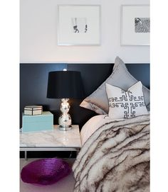 """Eisen often calls on """"unexpected touches"""" when she's styling a home. Here, she created a dramatic headboard with inexpensive Ikea desktops propped against the wall. The headboard's dark hue really pops against the light wall. For another decorating twist, she rotated pillow shams to show off diamonds instead of squares. Fashion your own headboard with these Ikea desks.   - ELLEDecor.com"""