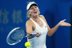 Maria Sharapova Photos: China Open: Day 5. Maria Sharapova of Russia returns a shot against Carla Suarez Navarro of Spain during day five of the China Open at the China National Tennis Center on October 1, 2014 in Beijing, China.