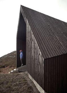 Die dunkle Zedernholzfassade nimmt die raue Umgebung in sich auf.