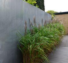 Grassen met betonlook muur