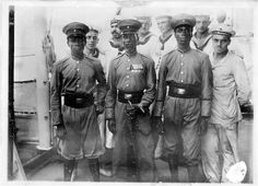 Togo Polizeitruppe NCOs with German Sailors The Polizeitruppe wear the Togo khaki uniform with peaked cap. Interestingly all three have khaki shoulder straps on their uniforms which were not common practice in Togo. Note the red rank chevrons on both arms. The NCO on the right has a single chevron and is therefore a Gefreiter, on the left of the photo is an Unteroffizier with two chevrons. The figure in the centre is the most interesting with the four chevrons and a sword of the Feldwebel…