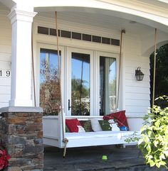 This front porch swing has Christmas pillows on display