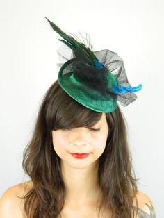 Blue Peacock Fascinator Headpiece Hat  This statement piece is as simple as it is striking.  Looking to spicy up that classic little black dress? Look no further, this elegant accessory is all you need.  The round sinamay base in dark green is 16.5cm wide (side to side), 19cm long (front to back). The overall piece is approximately 31cm at its widest point and 9cm high. Secures to the hair with an elastic.  You are buying the piece you see in the photos. I have tried my utmost to show the…