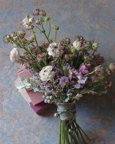 Picture this: a mix of violet, lavender, and white, plus a few blooms reaching for the sky. This clutch of tulips, lilacs, sweetpeas, ranunculus, and astrantia might as well have been lifted straight from a Dutch still life. The masterstroke? A wide silver bangle, slipped over a velveteen ribbon, encircling the stems.