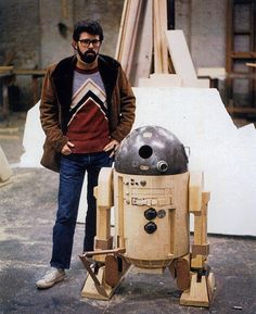Writer/director George Lucas inspects an early prototype of the R2-D2 robot at Industrial Light and Magic, circa 1975.  Lucas' idea for a space western was rejected by Universal, Walt Disney, and United Artists. 20th Century Fox paid him $150,000 to write and direct the film despite not having a visual effects department. This prompted George to create ILM where many of the effects that would transform Hollywood would be created.
