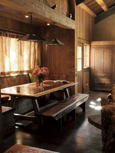 A custom picnic table and built-in bench serve as a dining spot in this country home. Mission-style metal pendant lights illuminate the table's rich wood surface. Dark-brown cement floors and undyed-linen curtains blend in with the home's natural setting. But this place isn't as rustic as it appears -- the cabinet in the corner houses a high-end refrigerator.