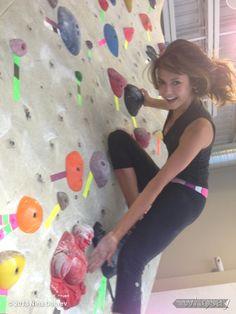 Nina Dobrev wearing lululemon whisper yoga tank while rock climbing.