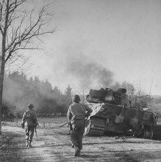 An American patrol moves toward a smoldering German Royal tank, with its crew still inside during the major German offensive of WWII which came to be known as the Battle of the Bulge, December 1944.