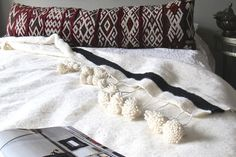Our pom pom blankets are hand-loomed in the souks of Marrakech. Made of 100% wool with a handmade long hanging pom pom edge, this blanket is the perfect bed cover or throw. They also look fantastic hanging behind a bed or draped over a large chair.