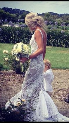 Gorgeous wedding dress. Very Boho Chic and perfect for a summer wedding at the beach. Looks like she just picked a handful of wildflowers!