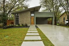 Marvelous Exterior Design for Modern Homes: Carport With Concrete Flooring For Driveway Entrance And Grass With Concrete Walkway In Front Door For House Tours With Planter And Roof Line Also Shed Roof In Modern Homes ~ parsegallery.com Decorating Inspiration
