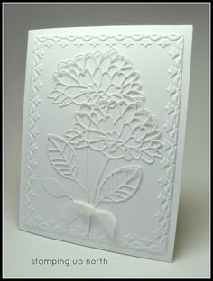 handmade card from stamping up north ... white on white ... lots of texture ... embossing folder frame ... lacy die cut flowers ... white ribbon in a knot ... wonderful card!