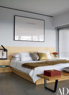 Limited-edition Je t'aime pillowcases by Louise Bourgeois from the Tate Modern grace the master bedroom; the work on paper is by Richard Long, and the bench at the foot of the bed is by Nelson for Herman Miller   archdigest.com