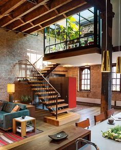 Reclaimed materials, including a retractable glass roof and architectural metalwork, help make this restored TriBeCa loft both sustainable and rustic. Andrew Franz Architect included fluid connections with the rooftop from the mezzanine and open interior to optimize the possibilities for entertaining and enjoying sunlight from the inside. #architecture #interiors #design #interiordesign @andrewfranzarchitect