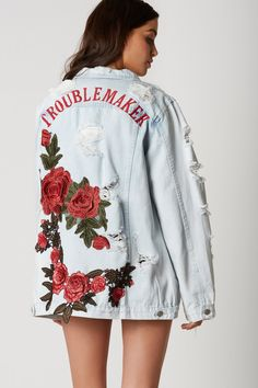 Heavily distressed denim jacket with trendy oversized fit. Bold floral patches and embroidery in back with classic button front closure.