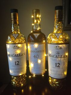 Macallan Scotch whiskey bottle centerpieces party decorations, 40th birthday.  Large (empty) 1.75 L macallan bottles filled with fairy lights and gold metallic shred.
