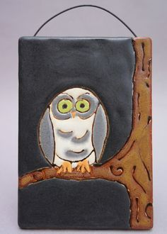 Small gray owl on a tree branch in a dark sky on a handmade ceramic tile, ready to hang.