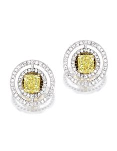 PAIR OF 18 KARAT TWO-COLOR GOLD, FANCY YELLOW DIAMOND AND DIAMOND EARRINGS, GRAFF. Centered by two cut-cornered rectangular modified brilliant-cut Fancy Yellow diamonds weighing 1.08 and 1.06 carats, the circular surrounds set with round diamonds weighing approximately .90 carat, signed Graff, numbered 5304.