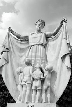marble antique statue symbolizing mother protecting her children, monumental cemetery in Florence, Italy