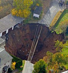 An aerial view shows a giant landslide under a residential street taking a car with it and leaving another car hanging over the edge in Schmalkalden, central Germany, Nov. 1, 2010. The cause of the landslide is yet unclear unclear. Residents were evacuated from 23 buildings. Nobody was injured.  (Jens Meyer/AP Photo)