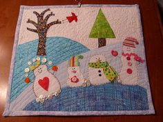 cute! - I love the variety of fabrics and snowman shapes. The buttons are a nice addition too. - - - Snowman mini quilt.