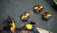 "Paddling to school in homemade personal ""boats"" !  Lagos, Nigeria."