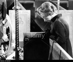 Widowed Ethel Kennedy kneels in prayer near the flag-draped bier of her husband. June 8, 1968.