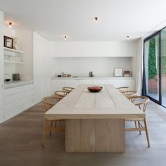 Beautiful and symplistic white kitchen diner, marble worktops, wooden floor