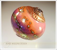 Large hollow focal bead that has fine silver droplets & deep violet frit for decoration, gold fumed, and finished with copper bead caps that were textured with my custom rolling mill sheets. Renee Wiggins Design, 2014.
