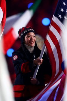 Hockey player Julie Chu of the United States enters with the flag during the 2014 Sochi Winter Olympics Closing Ceremony at Fisht Olympic Stadium