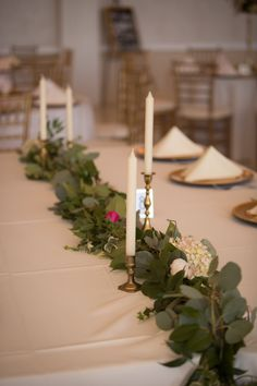 Foliage garland runner with fresh  hydrangea and roses. Taper candles tucked into the garland