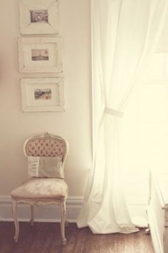 flowy white curtains, framed vintage postcards, vintage chair with tiny pillow.