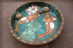 This bird bath bowl is made from stained glass and river rock.