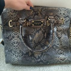 Like new Michael Kors Snakeskin Large Purse Beautiful Bag. Condition is like new. There is one little stain on the inside of the bag on the lining. Authentic Michael Kors. Python embossed leather. Magnetic snap closure. Two big pockets, one middle zip pocket, and 3 small pockets on the inside. May be open to price negotiations. MICHAEL Michael Kors Bags Totes
