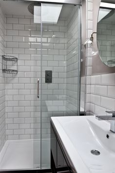 Use grey grout to make your white tiles stand out & use contrasting shapes such as round mirror & pendant lights for an ultra stylish finish