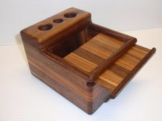 Vape Desktop Storage  $49.99  Handmade in Texas from select Walnut and Pecan hardwoods Dimensions are 6″x 5″x 3.75″ (LxWxH). The storage compartment can hold your juice bottles, tanks, tips, coils, or your favorite accessories. Three battery bays with 1″ openings. Some images shown are past custom orders.
